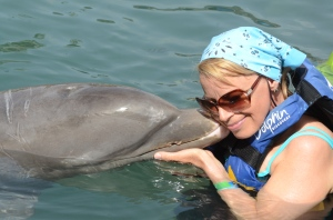 Jan in the water with a dolphin.